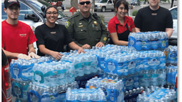 Group of people with tons of cases of bottled water